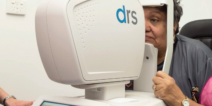 Woman having her eye scanned by machine