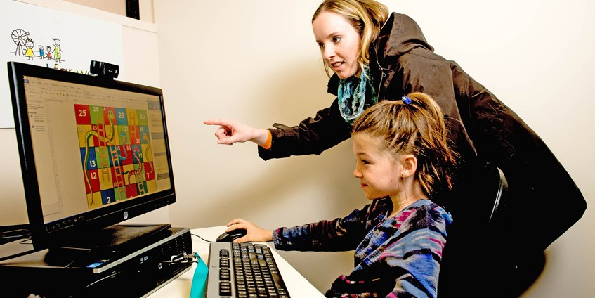 Young woman helping a young girl use a computer