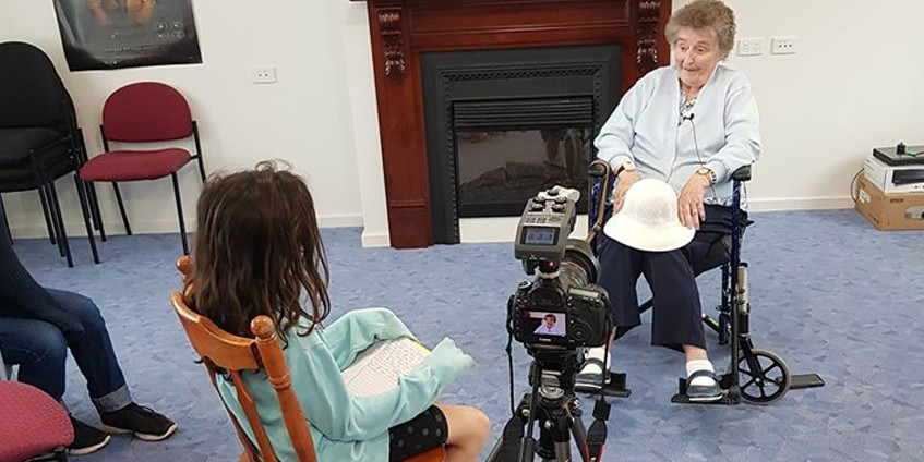 Young girl interviewing elderly woman