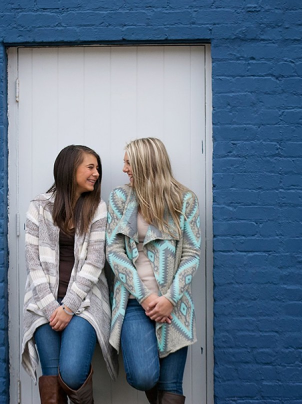 Teenage girls leaning on blue brick wall