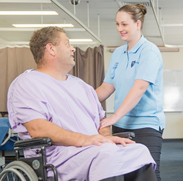 Man in wheelchair being assisted by nurse