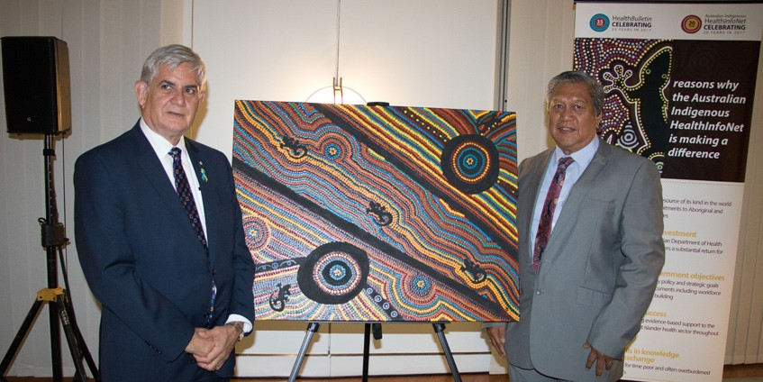 Minister Ken Wyatt and artist Mick Adams with the artwork commissioned for the Australian Indigenous HealthInfonet's 20th anniversary