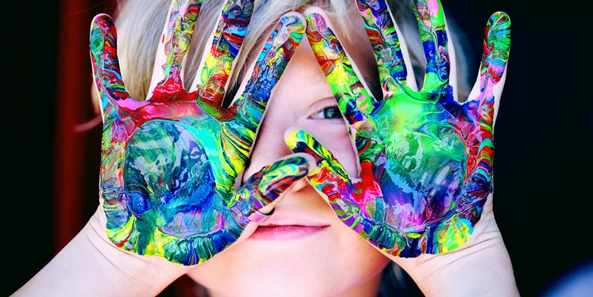 Boy with coloured paint on hands in front of his face