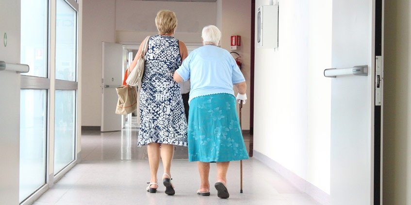 Elderly woman with younger woman in medical facility