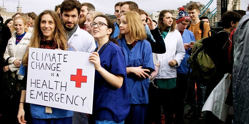 People marching with sign Climate Change is a Health Emergency