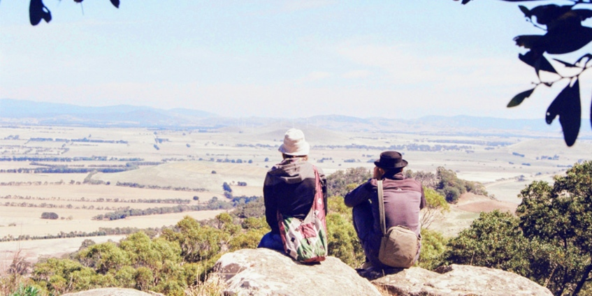 Two people sitting on rocks looking out over valley