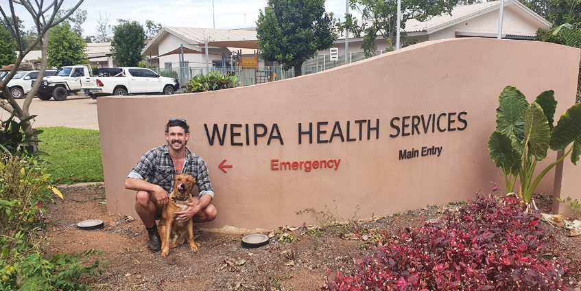 Man and his dog in front of Weipa Health Services sign