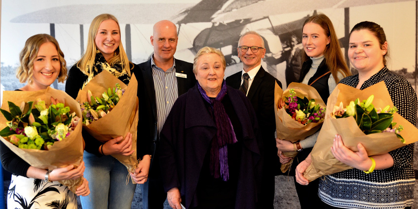 Winners of the  Give Them Wings scholarships. Four young women holding flowers presented by two men and a woman.