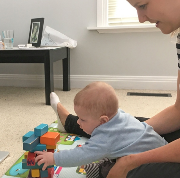 Baby playing with blocks in front of laptop supported by mother