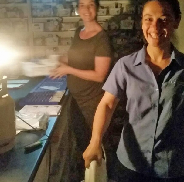 Pharmacy staff working during the bushfire and being creative with heating the iron to seal the medicine pack.