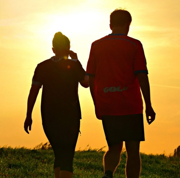 Silhouette of man and woman excercising against a orange sky