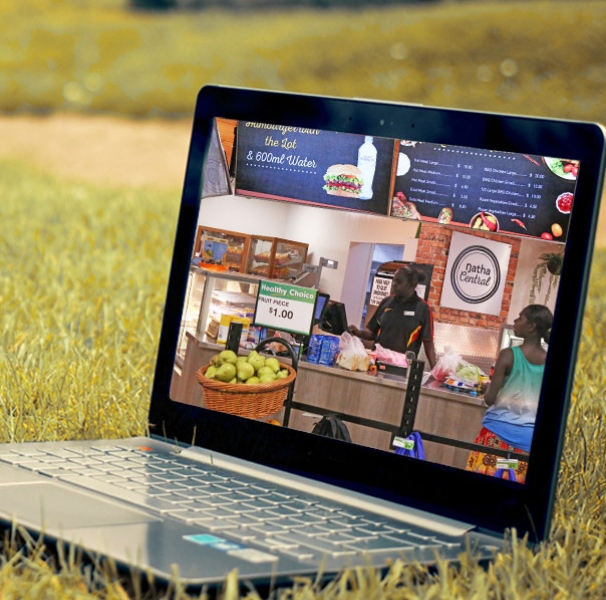 Laptop on a grassy area with a screen of a remote grocery shop