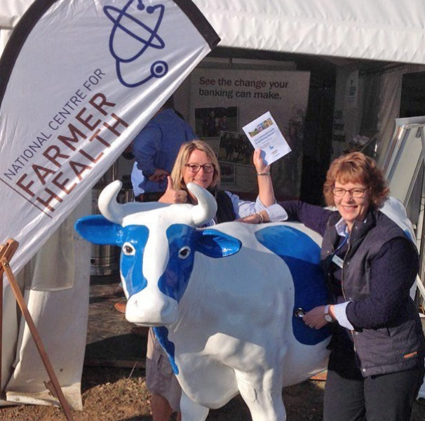 National Centre for Farmer Health RNs Jeanne van De Geest Dekker and Carolyn Alkemade showcasing a health passport at a rural field day.
