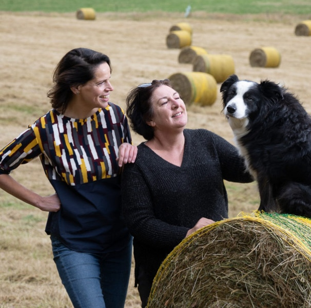 Two women with dog on a hay bail.