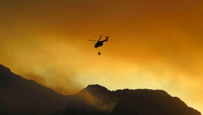 fire fighting helicopter over smokey bush fire